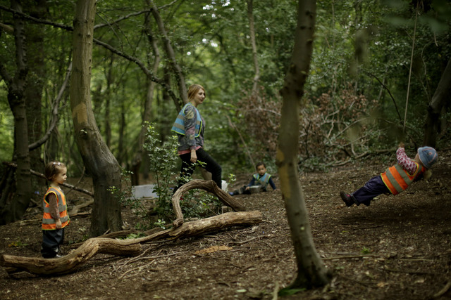 "In this photo taken Tuesday, July 8, 2014, children play at the ""Into the Woods"" outdoor children's nursery in Queen's Wood, in the Highgate area of north London. In the heart of north L ..."
