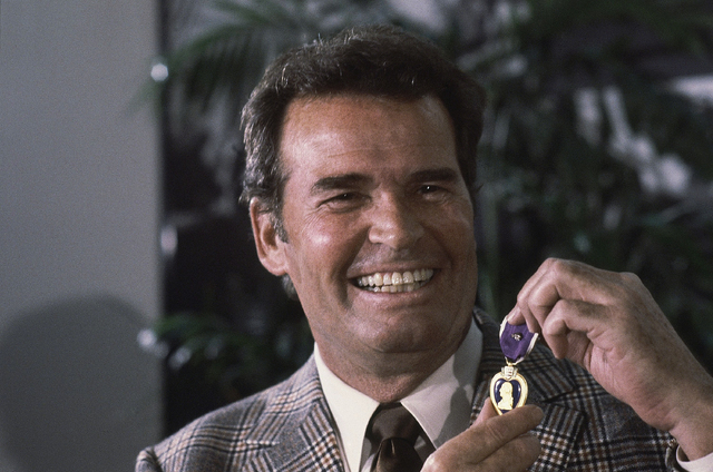 Actor James Garner, left, smiles as he holds up the Purple Heart medal presented to him in a ceremony in this Monday, Jan. 24, 1983 file photo taken Los Angeles, Calif. Garner was wounded in April ...