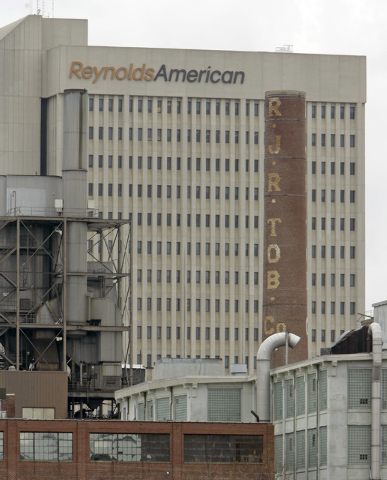 In this Feb. 6, 2008 photo, a smokestack of an old R.J. Reynolds Tobacco plant frames the Reynolds American building in Winston-Salem, N.C., A Florida jury has slammed R.J. Reynolds Tobacco Co. wi ...