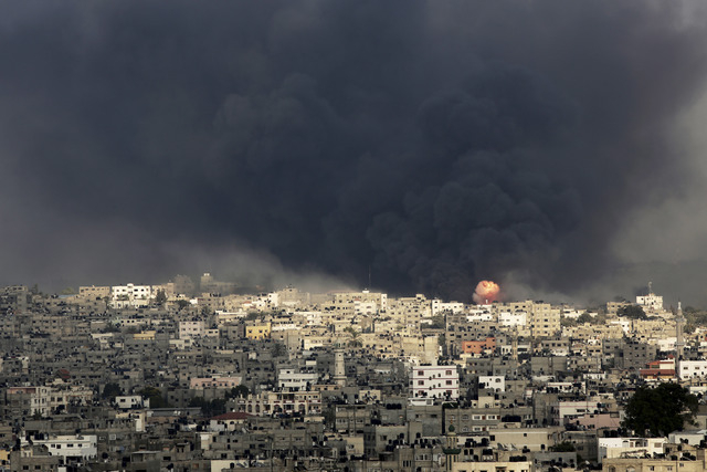 Smoke and flare of an explosion rise after an Israeli missile hit the Shijaiyah neighborhood in Gaza City, northern Gaza Strip, Sunday, July 20, 2014. The neighborhood came under heavy tank fire S ...