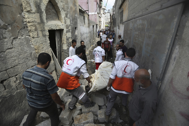 Palestinian medics carry a dead body found under the rubble of a home destroyed by an Israeli strike in the Shajaiyeh neighborhood of Gaza City, northern Gaza Strip, Sunday, July 20, 2014. Hundred ...