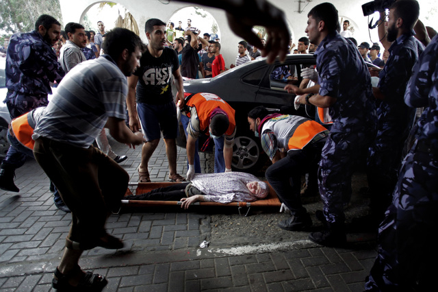 Palestinian medics carry a wounded woman to an emergency room at Shifa hospital in Gaza City, Sunday, July 20, 2014. Hundreds of panicked residents have fled a Gaza City neighborhood which they sa ...