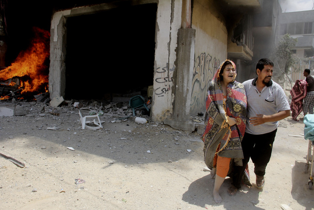 A Palestinian man helps a wounded woman in front of the Al Mughrabi family building following an Israeli air strike that hit their home in Rafah, Sunday, July 20, 2014. One woman and her 2-year-ol ...
