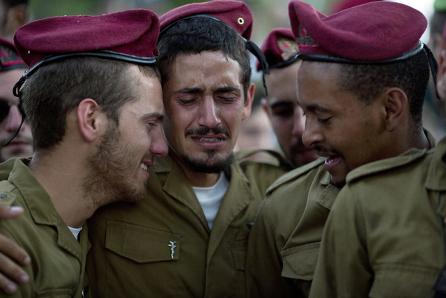 Israeli soldiers of the Paratroopers Brigade mourn over the grave of Sgt. Bnaya Rubel during his funeral at the military cemetery in Holon, Israel, Sunday, July 20, 2014. Rubel was killed while fi ...