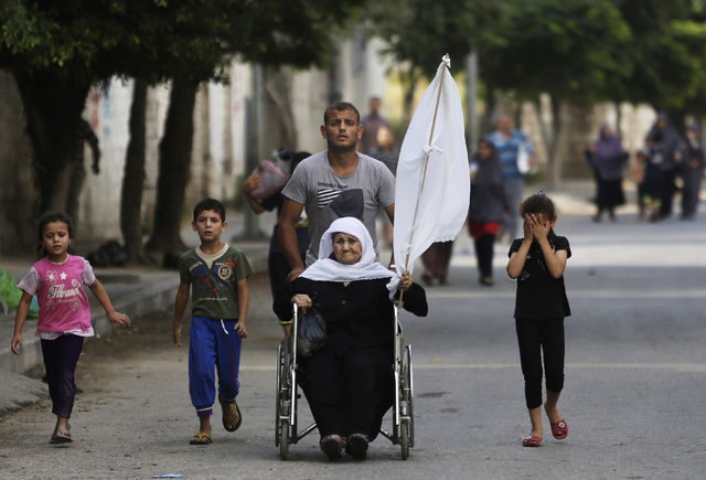 A Palestinian wheels an elderly woman holding a white flag as they flee their homes in the Shajaiyeh neighborhood of Gaza City, northern Gaza Strip, Sunday, July 20, 2014. Hundreds of panicked res ...