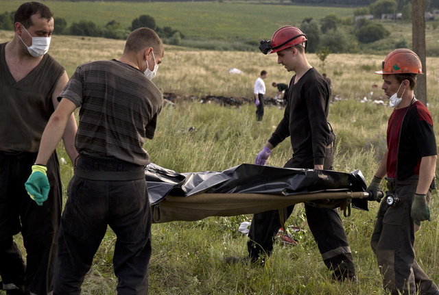 Ukrainian miners carry the body of a victim at the crash site of Malaysia Airlines Flight 17 near the village of Hrabove, eastern Ukraine, Saturday, July 19, 2014. World leaders demanded Friday th ...