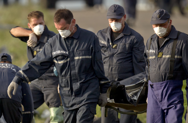 Emergency workers carry the body of a victim at the crash site of Malaysia Airlines Flight 17 near the village of Hrabove, eastern Ukraine, Saturday, July 19, 2014. World leaders demanded Friday t ...