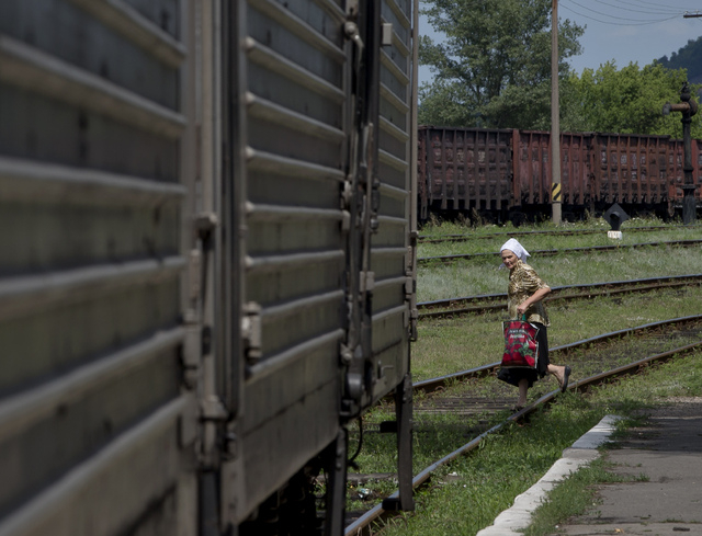 A woman looks at a refrigerated train loaded with the bodies of victims, in Torez, eastern Ukraine, 15 kilometers (9 miles) from  the crash site of Malaysia Airlines Flight 17, Sunday, July 20, 20 ...