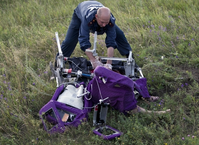 An emergency worker cuts through aircraft seat belts to free the body of a victim at the crash site of Malaysia Airlines Flight 17 near the village of Hrabove, eastern Ukraine, Saturday, July 19,  ...