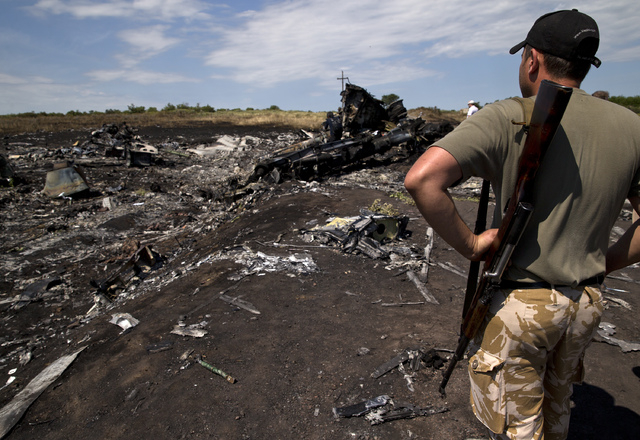 An armed man looks at charred debris at the crash site of Malaysia Airlines Flight 17 near the village of Hrabove, eastern Ukraine, Sunday, July 20, 2014. Armed rebels forced emergency workers to  ...