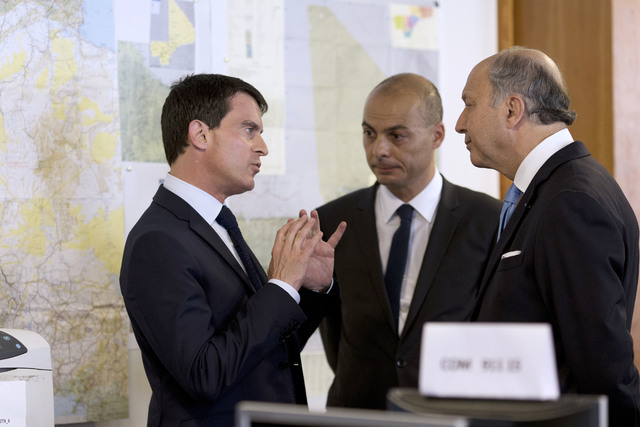 French Prime Minister Manuel Valls, left, speaks with French Foreign Affairs minister Laurent Fabius, right, and director of the French Foreign Affairs ministry's crisis center Didier Le Bret as t ...