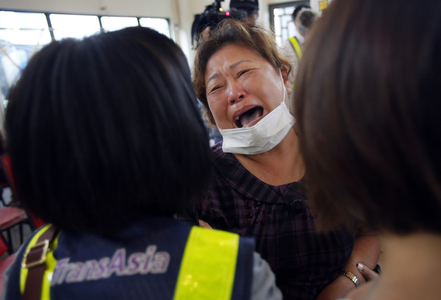 A relative of a victim in the TransAsia Airways flight GE222 crash breaks down during a funeral service on the Taiwan island of Penghu, Friday, July 25, 2014. Stormy weather on the trailing edge o ...