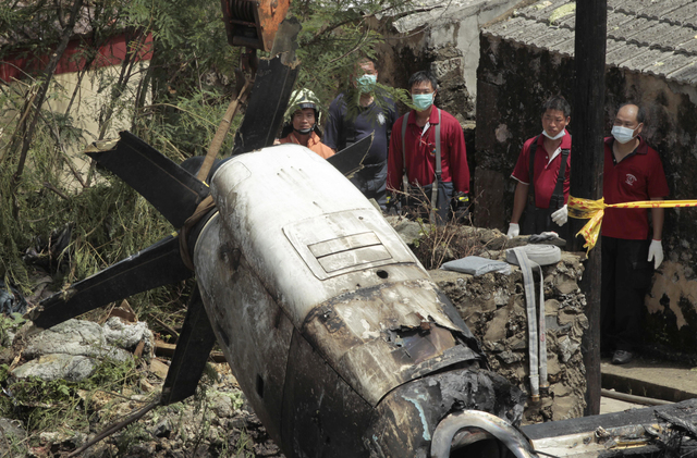 Emergency workers watch an engine lifted from the TransAsia Airways Flight GE222 crash site on the outlying Taiwan island of Penghu, Friday, July 25, 2014. Investigators on Friday were examining w ...