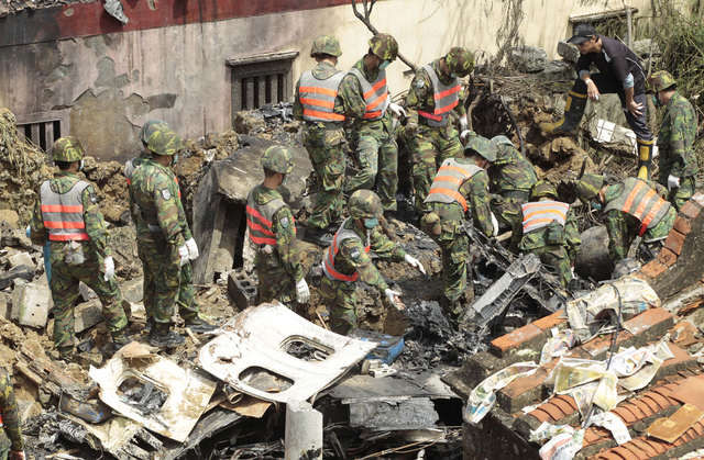 Soldiers remove debris from the TransAsia Airways flight GE222 crash site on the outlying Taiwanese island of Penghu, Friday, July 25, 2014. Investigators on Friday were examining wreckage and fli ...