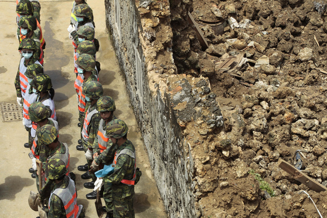 Soldiers prepare to remove debris at the site of TransAsia Airways Flight GE222 crash on the outlying Taiwan island of Penghu, Friday, July 25, 2014. Investigators on Friday were examining wreckag ...