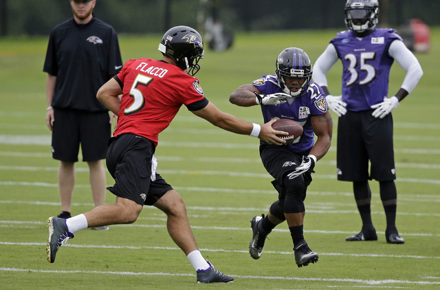 Baltimore Ravens quarterback Joe Flacco, left, hands off  to running back Ray Rice during a training camp practice, Thursday, July 24, 2014, at the team's practice facility in Owings Mills, Md. (A ...