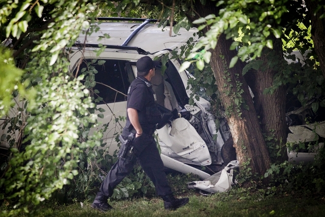 A police officer walks past the wreckage of a carjacked vehicle that police say hit a group of people on a corner in Philadelphia on Friday, July 25, 2014, killing two children and critically inju ...