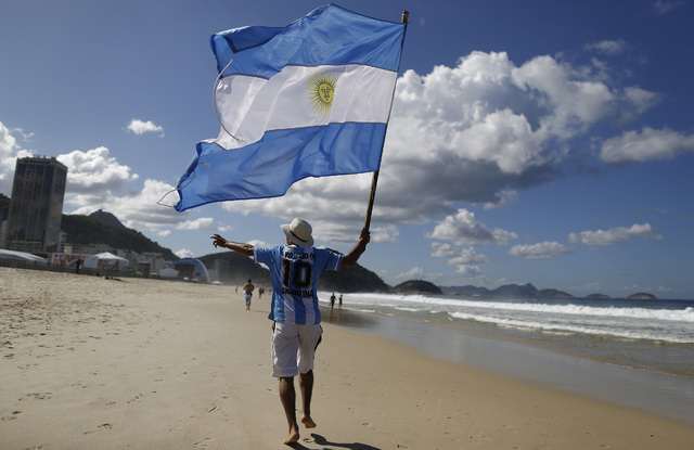In this  July 14, 2014, file photo, an Argentina soccer fan waves Argentina's national flag the morning after his team was defeated by Germany at the World Cup final, on Copacabana beach in Rio de ...