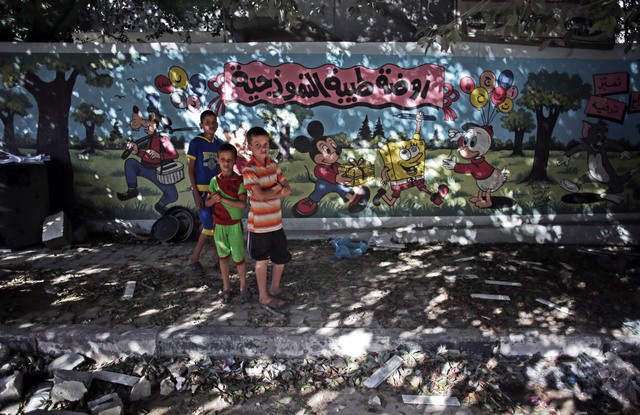 """Palestinian boys stand next to wall with murals and Arabic writing that reads """"Tiba standard nursery,"""" next to a destroyed house following an overnight Israeli strike in Gaza City Friday ..."""