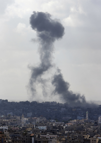 Smoke from an Israeli strike rises over the Gaza Strip, Friday, July 25, 2014. An Israeli defense official says the Israeli Security Cabinet is meeting to discuss international ceasefire efforts,  ...