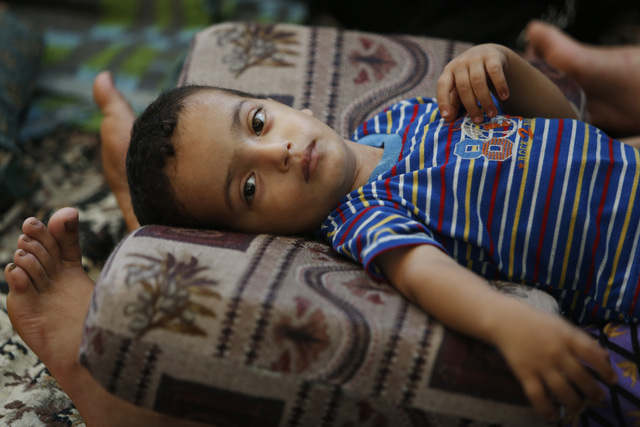Two and a half-year-old Muhammad Al Masri rests on his mother's legs in a classroom at a United Nations school where hundreds of families have sought refuge after fleeing their homes following hea ...
