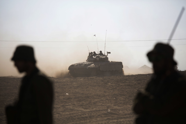 Israeli tank rides near the Israel and Gaza border Friday, July 25, 2014. Early Friday, Israeli warplanes struck tens of houses throughout the Gaza Strip as international efforts continue to broke ...