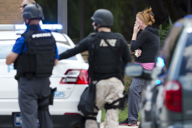 A hospital worker views police activity around the scene of a shooting Thursday, July 24, 2014,  at Mercy Fitzgerald Hospital in Darby, Pa. Police in suburban Philadelphia are investigating a shoo ...