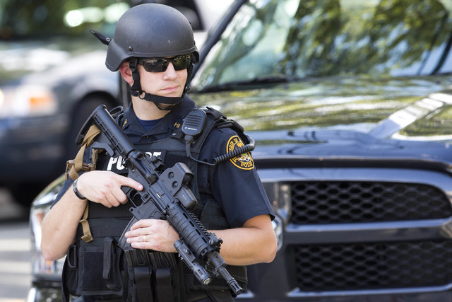 An officer stands guard near the scene of a shooting Thursday, July 24, 2014, at Mercy Fitzgerald Hospital in Darby, Pa. A doctor grazed by gunfire from a patient who had entered his office in a s ...