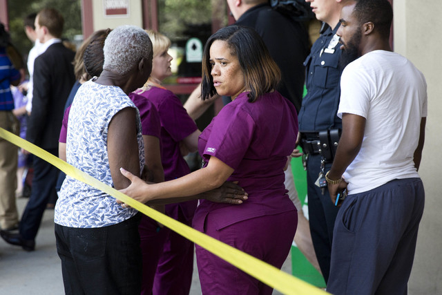 A hospital worker views police activity near the scene of a shooting at a wellness center attached to Mercy Fitzgerald Hospital in Darby, Pa., on Thursday, July 24, 2014. A doctor grazed by gunfir ...