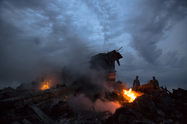 File - This July 17, 2014, file photo show people walking amongst the debris at the crash site of Malaysia Airlines Flight 17 near the village of Hrabove, eastern Ukraine.  Ukraine said the passen ...