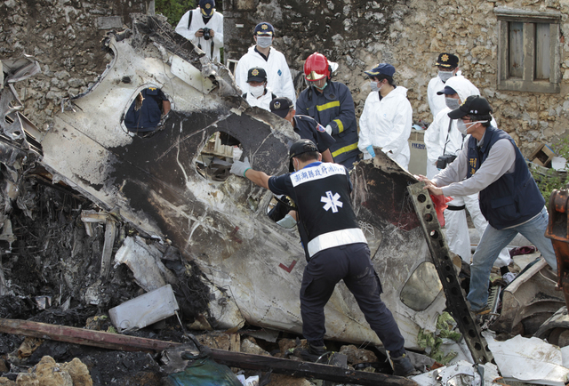 A forensic team recovers human remains among the wreckage of crashed TransAsia Airways flight GE222 on the outlying island of Penghu, Taiwan, Thursday, July 24, 2014. Stormy weather on the trailin ...
