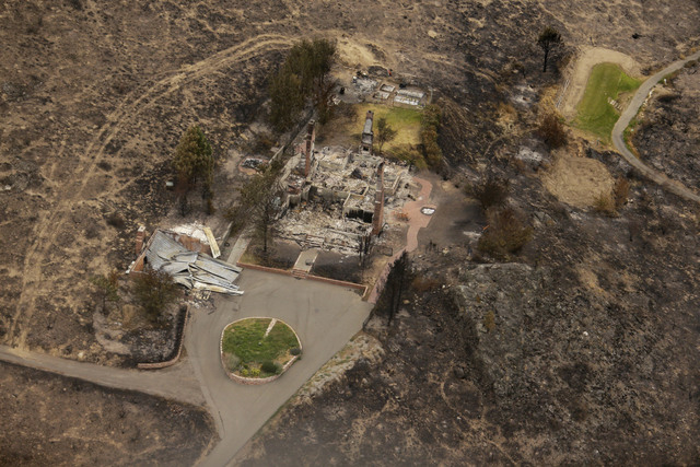 This aerial photo shows structures which were destroyed by wildfires near Pateros, Wash. on Thursday, July 24, 2014. Fire spokesman Pete Buist says the biggest wildfire in the state's history rema ...
