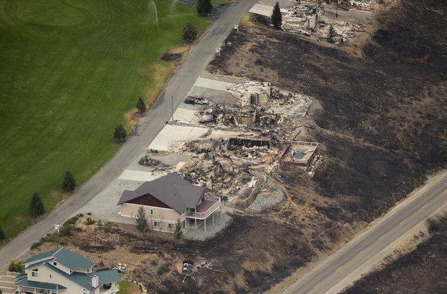 This aerial photo shows homes destroyed by wildfires near Pateros, Wash. on Thursday, July 24, 2014. Fire spokesman Pete Buist says the biggest wildfire in the state's history remains at 52 percen ...