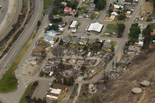 This aerial photo shows homes destroyed by wildfires in Pateros, Wash. on Thursday, July 24, 2014. Fire spokesman Pete Buist says the biggest wildfire in the state's history remains at 52 percent  ...