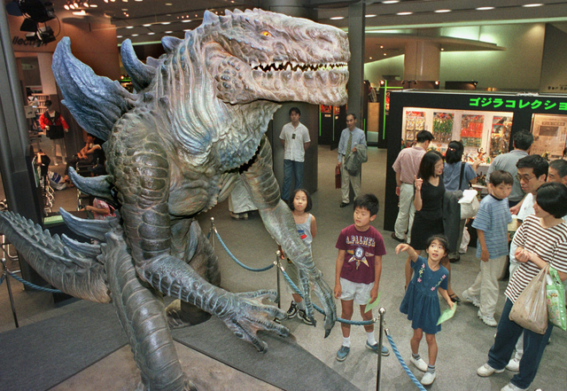 FILE - In this July 11, 1998 file photo, children look at a 2.7-meter-tall (9-foot) model of a 1998 Godzilla character in a Tokyo auto showroom. Yoshihiko Horie, 54, hated the 1998 Godzilla so muc ...