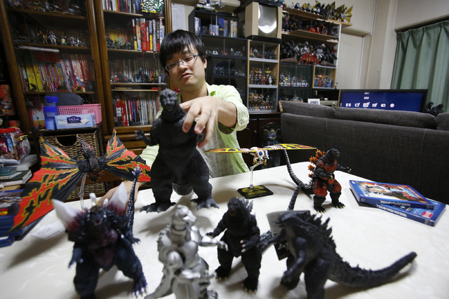 In this Tuesday, July 22, 2014 photo, Takeshi Maruyama picks up a model of the first Godzilla with some of his collections during an interview at his apartment in Yokohama, near Tokyo. Godzilla ap ...