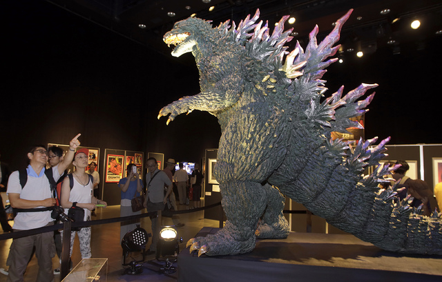 Japanese Godzilla devotees Yoshihiko Horie, left, and his wife Shizue look at a scale model of Godzilla at Godzilla Expo in Tokyo, Friday, July 25, 2014. Horie, a driver and husband of Godzilla fa ...