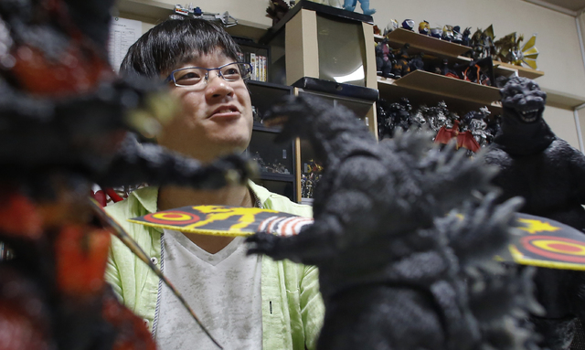 In this Tuesday, July 22, 2014 photo, Takeshi Maruyama, surrounded by his Godzilla and other monster figure collections, speaks during an interview at his apartment in Yokohama, near Tokyo. One of ...