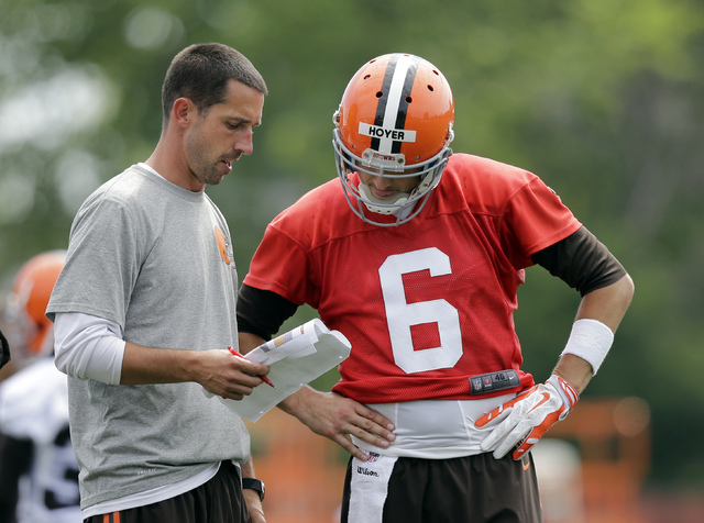 Cleveland Browns offensive coordinator Kyle Shanahan calls the play for quarterback Brian Hoyer (6) during NFL football training camp, Saturday, July 26, 2014, in Berea, Ohio. (AP Photo/Mark Duncan)