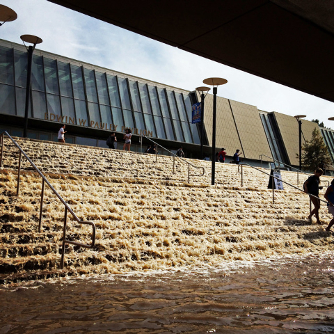 Water cascades down a stairway to a parking structure adjacent to Pauley Pavlion, home of UCLA basketball, background, after a 30-inch water main burst on nearby Sunset Boulevard Tuesday, July 29, ...