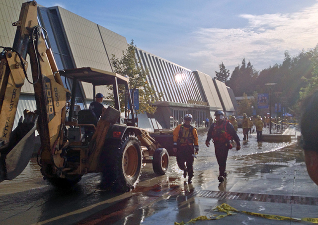 Workers approach Pauley Pavilion, home of UCLA basketball, left, after a 30-inch water main burst on nearby Sunset Boulevard Tuesday, July 29, 2014, in Los Angeles. Water also reached the playing  ...