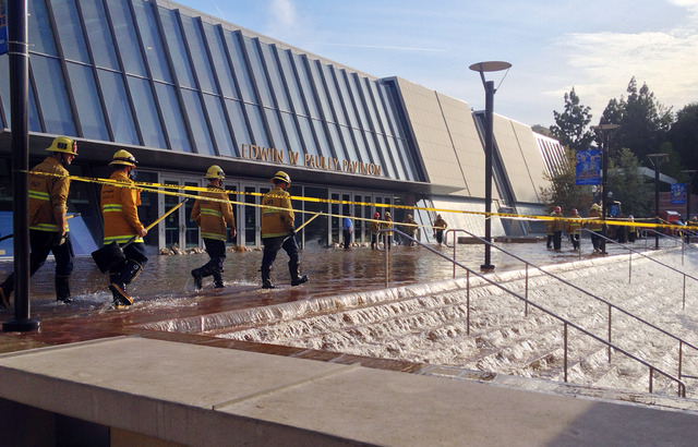 Water cascades down the stairs to a parking structure adjacent to the main entry doors of Pauley Pavilion, home of UCLA basketball, left, after a 30-inch water main burst on nearby Sunset Boulevar ...