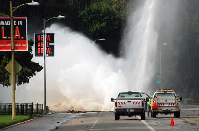 Water shoots in the air from a broken 30-inch water main under Sunset Boulevard, uphill from UCLA in the Westwood section of Los Angeles, Tuesday, July 29, 2014. The resulting flood inundated seve ...