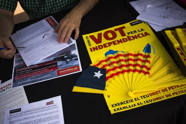 In this Oct. 20, 2013 photo, a man from Catalonia signs a public request asking the Parliament of Catalonia to approve a referendum to decide whether Catalonia should be an independent state, in C ...