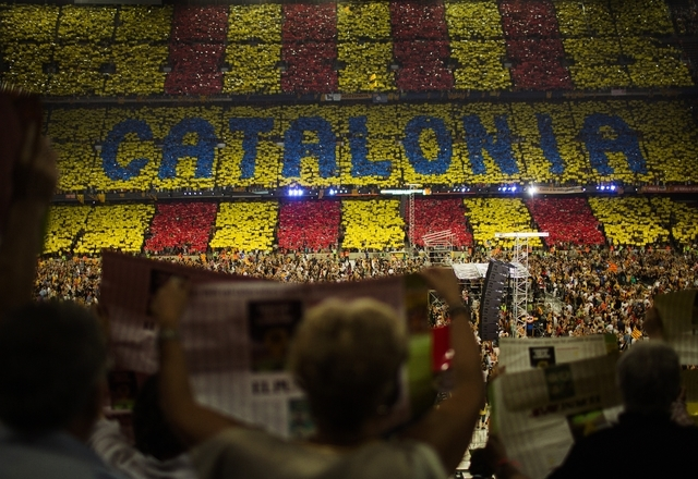 In this June 29, 2013, supporters make a mosaic with the words of Catalonia as they attend to a pro-independence festival in the Nou Camp stadium in Barcelona, Spain. Spanish Prime Minister Marian ...