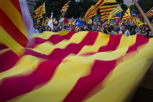 """In this Monday, June 2, 2014 photo, demonstrators wave a pro-independence """"estelada"""" flag during a protest calling for the independence and the implementation of the republic in Cataloni ..."""