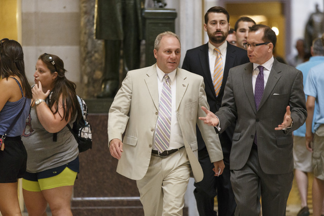 Rep. Steve Scalise, R-La., the incoming House GOP whip, walks between tourists and reporters in Statuary Hall on the way to the House chamber, at the Capitol in Washington, Wednesday, July 30, 201 ...