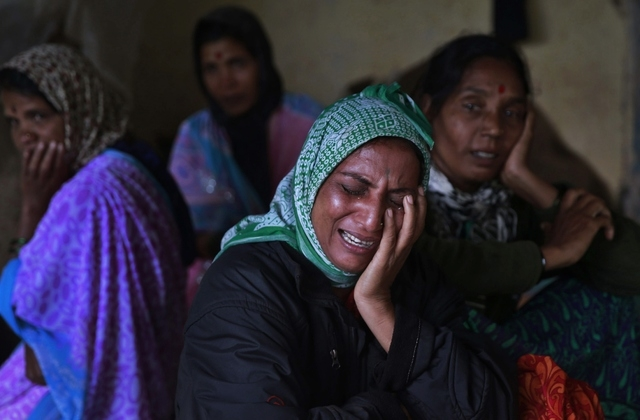 Relatives wail after seeing the body of a victim after a massive landslide in Malin village in Pune district of western Maharashtra state, India, Thursday, July 31, 2014. Two days of torrential ra ...
