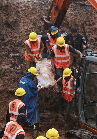 Rescue workers carry the body of a victim after a massive landslide in Malin village in Pune district of western Maharashtra state, India, Thursday, July 31, 2014. Two days of torrential rains tri ...