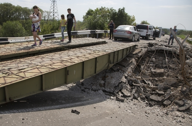 People walk across an exploded bridge near the village of Debaltseve, Donetsk region, eastern Ukraine, Thursday, July 31, 2014. (AP Photo/Dmitry Lovetsky)